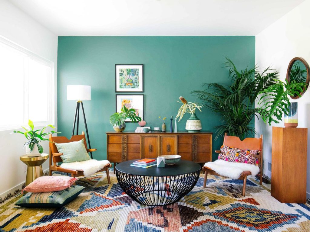 Care-free, accent wall of dark teal green, relaxed chairs and pillows, mix of colors, houseplants,