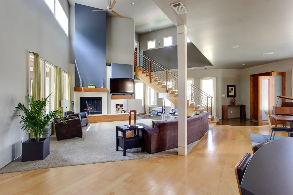 Muted tones with accent color, light-colored hardwood floors, living room with staircase in back right-center, natural lighting, spacious