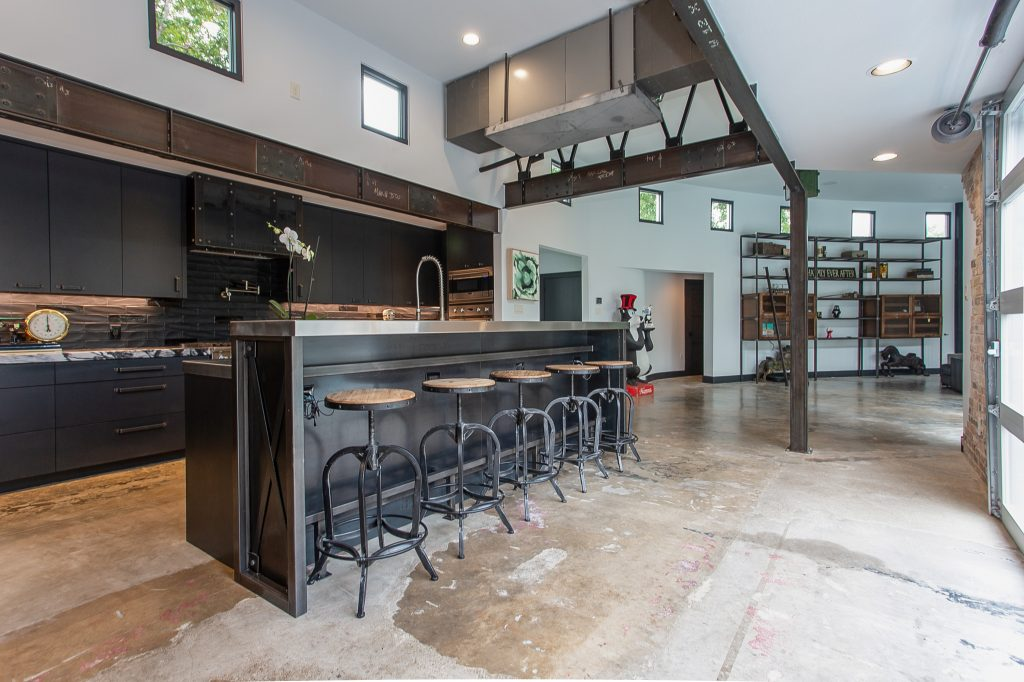 Concrete floors, metal accents, exposed lighting, metal pipig used for decor and furnishings, garage door style windows, metal grsting in kitchen for cabinets, wood accents