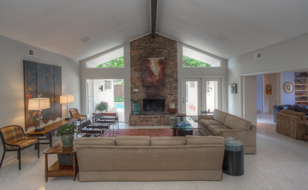 Well-lit, Angular ceilings, muted tones with accent colors from decor, tile flooring, floor-to-ceiling brick fireplace