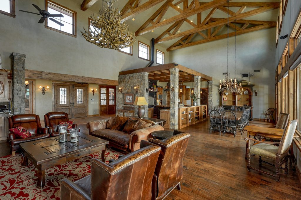 Rich brown color palette, leather furniture, antle chandelier, hardwood floows, open living space into kitchen and dining, large wooden beams in ceiling, catherdral ceilings, large windows, think, sturdy wooden furniture