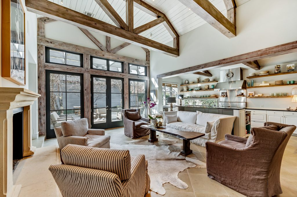 Large open living room that flows to kitchen, open cabinetry so as to see the contents, large windows, animal-skin-esque rugs, large wooden accent beams with wood accents in windows and kitchen, off whites and dark greens for accent, tile flooring